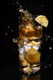 Pezzo di caduta di ghiaccio in un vetro di alta qualità di whiskey che sta su un altro vetro pieno della fetta del limone e del g Immagini Stock