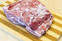 Pezzo di carne congelato sulla tavola fotografia stock