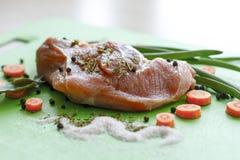 Pezzo di carne crudo con le spezie, con le erbe ed il primo piano delle carote Fotografia Stock
