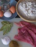 Pezzo di carne e sale e spezie, uova, latte e farina sul tagliere fotografia stock