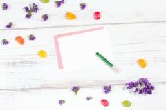 Pezzo di carta in bianco ed il pastello su fondo bianco con i fiori lilla e le caramelle variopinte Immagine Stock Libera da Diritti