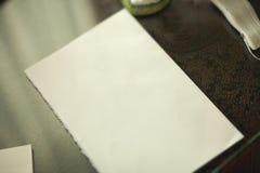 Pezzo di carta che si trova sulla tavola nell'ambito della luce calda di tramonto Immagine Stock Libera da Diritti