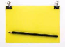 Pezzo di carta giallo con le graffette nere e la matita nera Immagini Stock