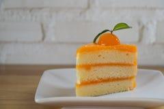 Pezzo di dolce arancio sulla tavola di legno Immagine Stock