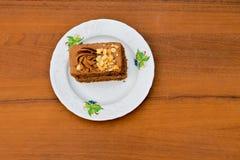 Pezzo di dolce con i dadi sul piatto sulla tavola di legno Vista superiore Fotografia Stock