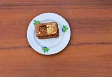 Pezzo di dolce con i dadi sul piatto sulla tavola di legno Vista superiore Fotografie Stock Libere da Diritti