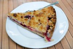 Pezzo di dolce delizioso con la ciliegia ed il lampone della bacca, con caramello su un piatto bianco sulla tavola di legno Fotografia Stock