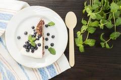 Pezzo di dolce dolce con la ciliegia, il mirtillo e la menta fotografia stock