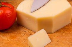 Pezzo di formaggio con un pomodoro su un bordo di wodden Fotografie Stock