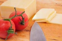 Pezzo di formaggio e fette di formaggio con i pomodori su un wodden Fotografie Stock Libere da Diritti