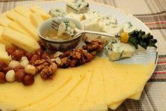 Pezzo di formaggio su una forcella, immersione in miele Fotografia Stock
