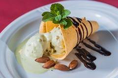 Pezzo di gelato con lo sciroppo di cioccolato, mandorle Fotografie Stock