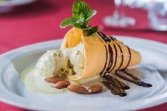 Pezzo di gelato con lo sciroppo di cioccolato, mandorle Fotografie Stock Libere da Diritti