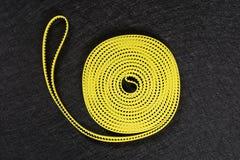 Pezzo di ingranaggi gialli della cinghia di gomma su un fondo scuro fotografia stock