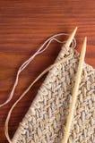 Pezzo di panno tricottato con gli aghi di legno sulla tavola di legno Fotografia Stock Libera da Diritti