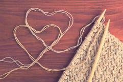 Pezzo di panno tricottato con gli aghi ed i cuori di legno del filo sull'annata di legno della tavola filtrata Fotografia Stock