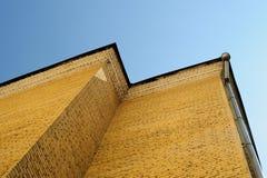 Pezzo di parete della casa con mattoni a vista con il chiaro cielo sui precedenti Immagini Stock