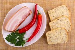 Pezzo di petto, peperoncini, prezzemolo in piatto, pezzi di pane sulla stuoia Vista superiore immagini stock