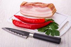 Pezzo di petto, peperoncini, prezzemolo sul tagliere, coltello sulla tavola immagini stock libere da diritti