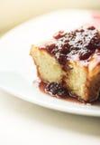 Pezzo di torta casalinga su un piatto con l'inceppamento della bacca Fotografie Stock
