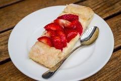 Pezzo di torta della fragola su un piatto con il cucchiaio Fotografia Stock