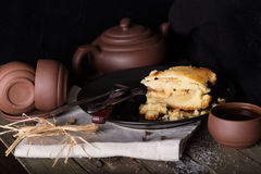 Pezzo di torta e di terraglie per tè su una vecchia tavola di legno Fotografia Stock