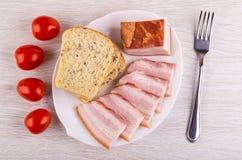 Pezzo, fette di petto, pane in piatto, forcella, ciliegia del pomodoro sulla tavola Vista superiore fotografie stock