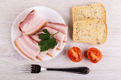 Pezzo, fette di petto, prezzemolo in piatto, pane, pomodori, forcella sulla tavola Vista superiore fotografie stock libere da diritti