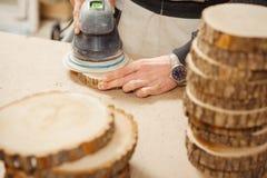 Pezzo in lavorazione rotondo di legno della tenuta maschio ed elaborare con la macchina per la frantumazione immagini stock