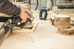 Pezzo in lavorazione rotondo di legno della tenuta maschio ed elaborare con la macchina per la frantumazione immagine stock libera da diritti