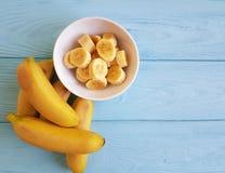Pezzo maturo dello spuntino del piatto della banana su un fondo di legno blu immagini stock libere da diritti