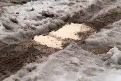 Pfütze auf der Straße im Winter Stockbilder