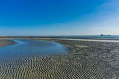 Pfütze spaltete sich vom Meer auf einem sandigen Strand auf Lizenzfreies Stockbild