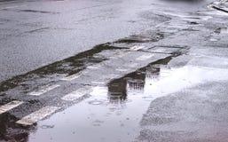 Pfützen des Wassers auf einer überschwemmten Straße im Vereinigten Königreich lizenzfreies stockbild