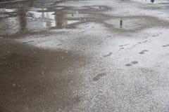 Pfützen und slushy Schnee mit Abdrücken Lizenzfreie Stockbilder