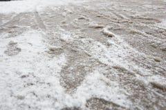 Pfützen und slushy Schnee mit Abdrücken Stockbild