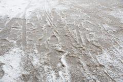Pfützen und slushy Schnee mit Abdrücken Stockbilder