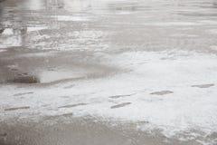 Pfützen und slushy Schnee mit Abdrücken Lizenzfreies Stockfoto