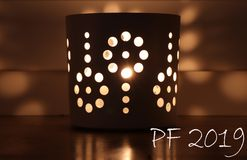PF 2019 greeting card with candle in cup with a holes which divide the light into many beautiful shades. Wish you all the best.  stock photo