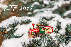 PF 2017 - train rouge de jouet de Noël sur le sapin neigeux de branche Image libre de droits