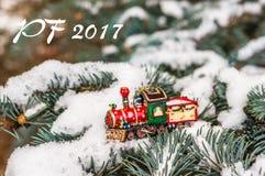 PF 2017 - tren rojo del juguete de la Navidad en abeto nevoso de la rama Imagen de archivo libre de regalías