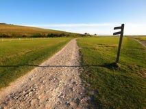 Pfad entlang grünem Feld mit Signage Stockfotos