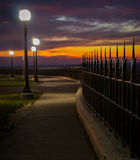 Pfad-Gehweg entlang Eisenzaun am Abend Stockbilder