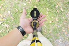 Pfadfinder benutzen den Kompass, um zu reisen Setzen Sie es auf Ihre Hand für leistungsfähigen Gebrauch lizenzfreie stockbilder