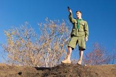 Pfadfinder, der auf einem Felsen nimmt eine Kompasslesung steht Stockbilder