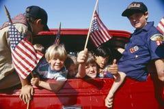 Pfadfinder, die amerikanische Flaggen wellenartig bewegen Stockbilder