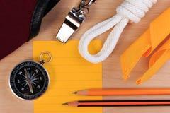 Pfadfinderseil-, -schal-, -pfeifen-, -kompass-, -bleistift- und -papieranmerkung der Ordnung weiße Lizenzfreies Stockfoto