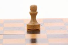 Pfand auf einem hölzernen Schachbrett Stockfotografie