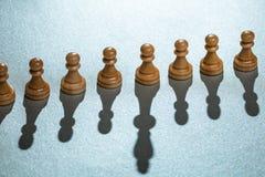 Pfand-Schachfiguren mit einer, die langen Schatten hat lizenzfreies stockbild