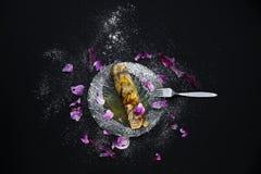 Pfannkuchen auf der Glasplatte verziert mit Zucker und dem Blumenblatt Lizenzfreie Stockbilder